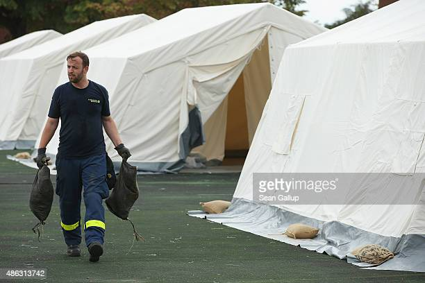 A member of Germany's THW emergency technical services helps to prepare tents at an emergency shortterm shelter for migrants under construction on...