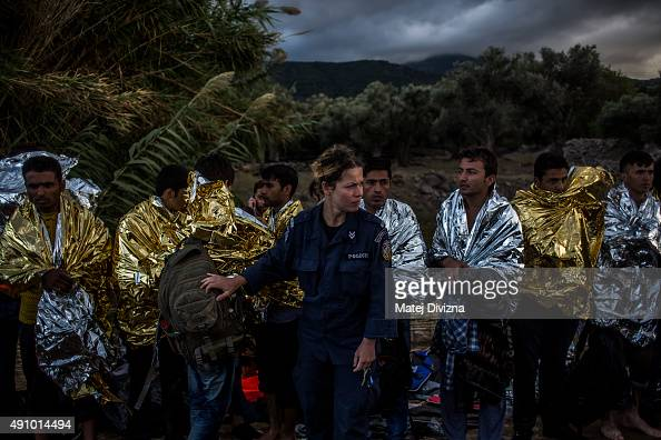 A member of Greece police lines up men wrapped with thermal blankets to shelter from cold as they arrived with other refugees on the shores of the...