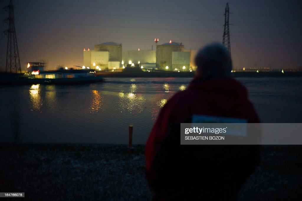 A member of Greenpeace looks at the nuclear powerplant of Fessenheim, in eastern France on March 28, 2013.