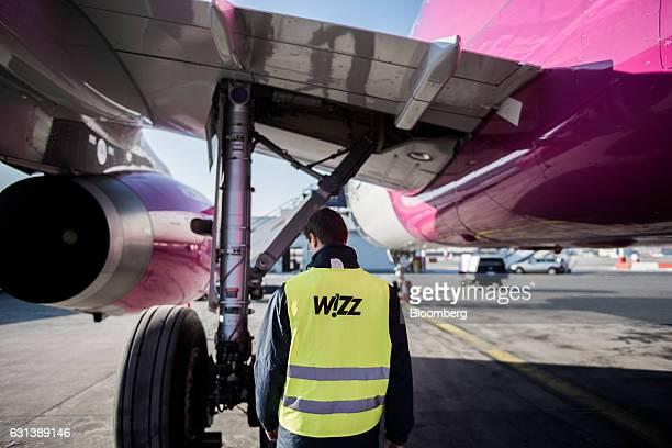 A member of ground crew carries out inspections on an Airbus A321231 passenger aircraft operated by Wizz Air Holdings Plc after landing at Liszt...