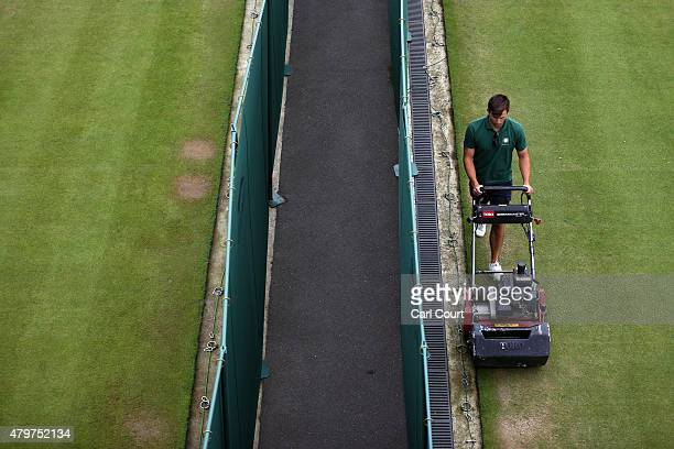 A member of ground mows a court ahead of play on day 8 of the Wimbledon Lawn Tennis Championships at the All England Lawn Tennis and Croquet Club on...