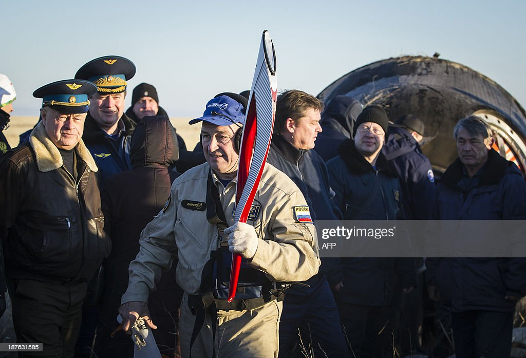 A member of ground personnel carries the torch of the 2014 Sochi Winter Olympic Games delivered from orbit in the Soyuz TMA-09M capsule after its landing in a remote area near the town of Zhezkazgan in central Kazakhstan on November 11, 2013. Three astronauts returned to Earth on November 11, after 66 days aboard the International Space Station, bringing back the Olympic torch back to the planet after a historic space walk. AFP PHOTO / Pool / Shamil Zhumatov