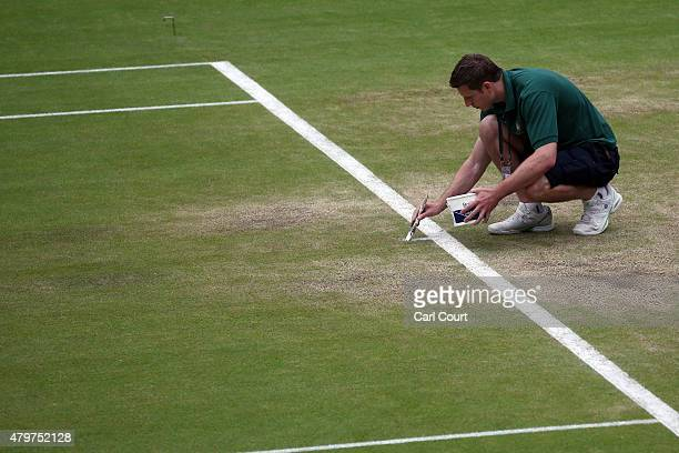 A member of ground staff hand paints a line on Centre Court ahead of play on day 8 of the Wimbledon Lawn Tennis Championships at the All England Lawn...