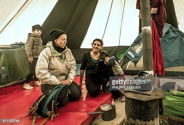 Member of 'Gynecologists without borders' speaks with a pregnant Kurd woman in a tent on February 18 2016 in the refugee and migrant camp in...