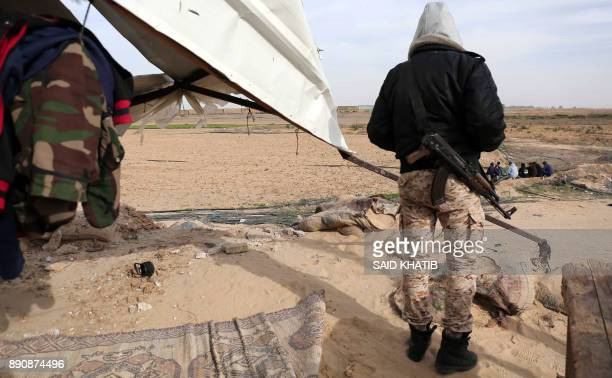 A member of Hamas' Ezzedine alQassam Brigades the armed wing of the Palestinian militant Hamas movement inspects damage incurred to a Hamas post that...