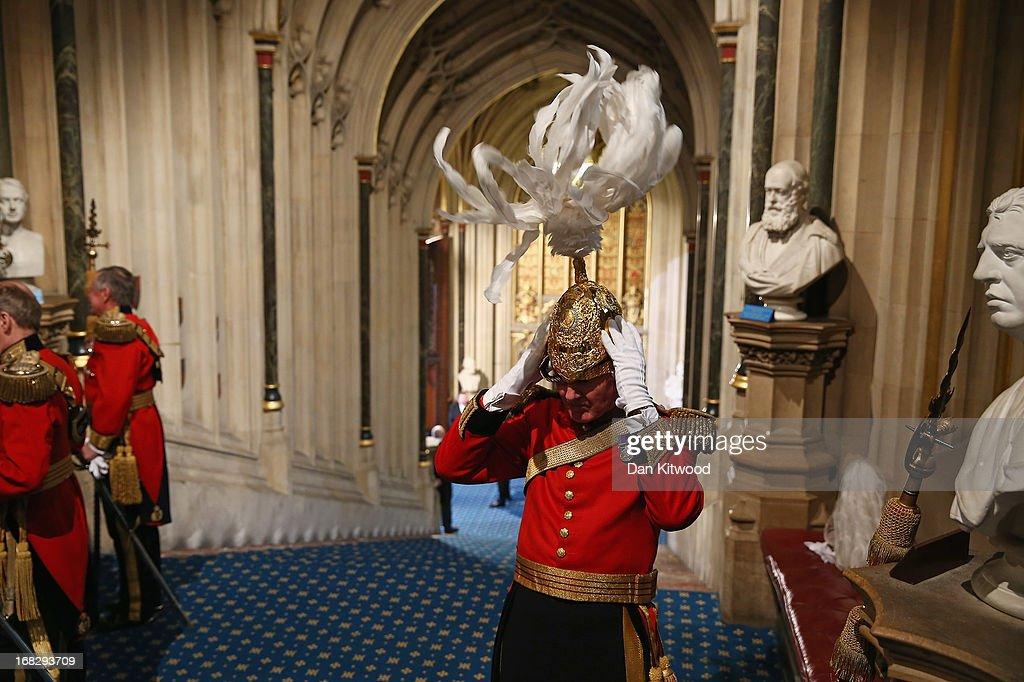 A member of Her Majesty's Body Guard of the Honourable Corps of Gentlemen at Arms adjusts his helmet ahead of the arrival of Queen Elizabeth II in the Norman Porch of the Palace of Westminster ahead of the State Opening of Parliament on May 8, 2013 in London, England. Queen Elizabeth II unveiled the coalition government's legislative programme in a speech delivered to Members of Parliament and Peers in The House of Lords. Proposed legislation is expected to be introduced on toughening immigration regulations, capping social care costs in England and setting a single state pension rate of 144 GBP per week.