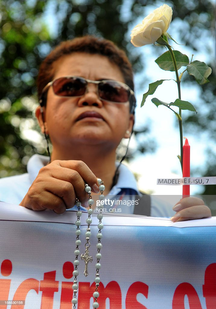 A member of human rights group, Volunteers Against Crime and Corruption (VACC), holds a white rose, a rosary and candles with names of those killed during the shooting at Sandy Hook Elementary School in Newtown, Connecticut in the US, during a prayer vigil in front of the US Embassy in Manila on December 18, 2012. Twenty children and six adults were reportedly killed by Adam Lanza, after he entered the school and opened fire. The massacre was the second-deadliest school shooting in the US after the 2007 Virginia Tech shooting.