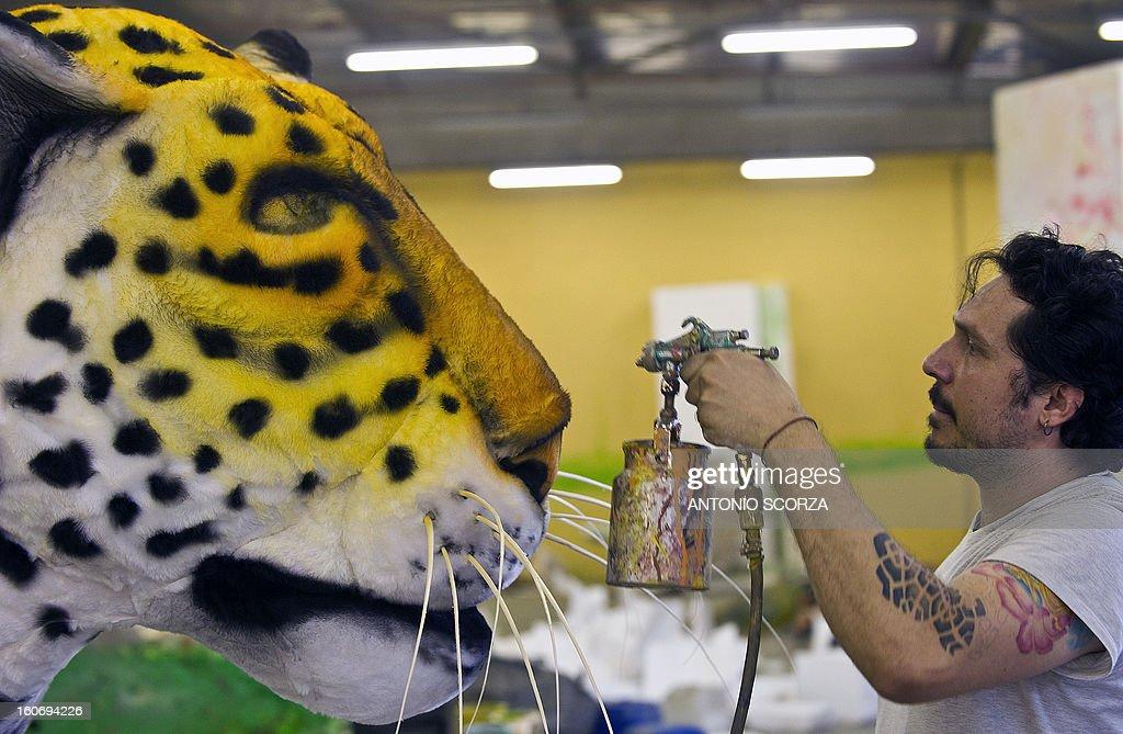A member of Imperatriz Leopoldinense samba school paints a yaguarete effigy during preparations for the famous carnival parade at the Sambodromo, on February 4, 2013 in Rio de Janeiro. The samba schools parade will be held next February 10 and 11.