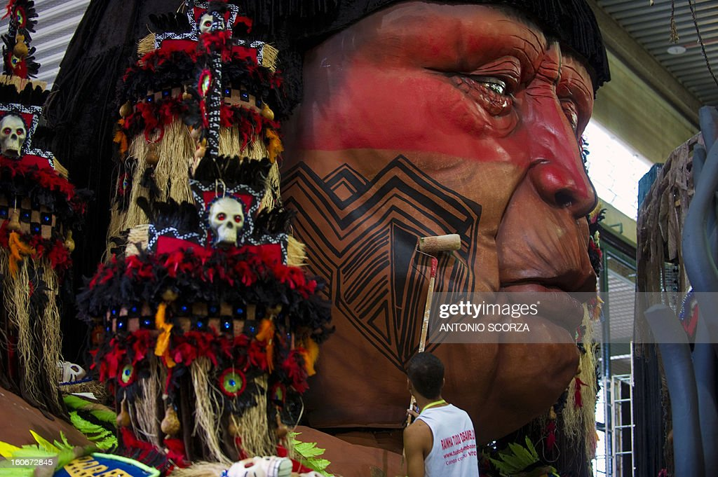 A member of Imperatriz Leopoldinense samba school paints an indigenous dummy face atop a float during preparations for the famous carnival parade at the Sambodromo, on February 4, 2013 in Rio de Janeiro. The samba schools parade will be held next February 10 and 11. AFP PHOTO/ANTONIO SCORZA