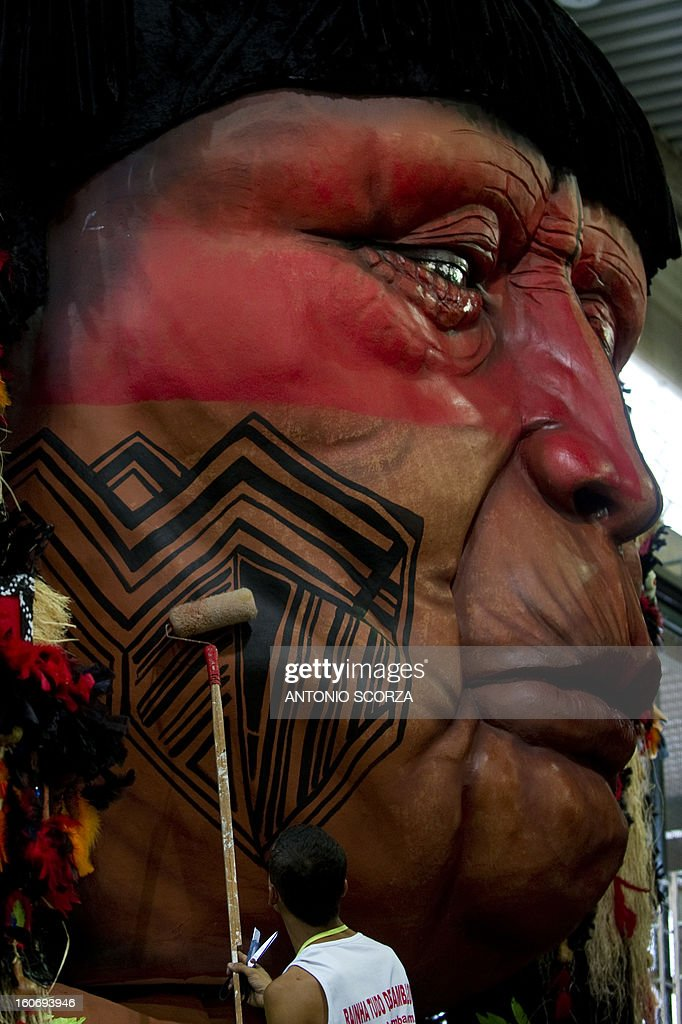 A member of Imperatriz Leopoldinense samba school paints an indigenous dummy face atop a float during preparations for the famous carnival parade at the Sambodromo, on February 4, 2013 in Rio de Janeiro. The samba schools parade will be held next February 10 and 11.