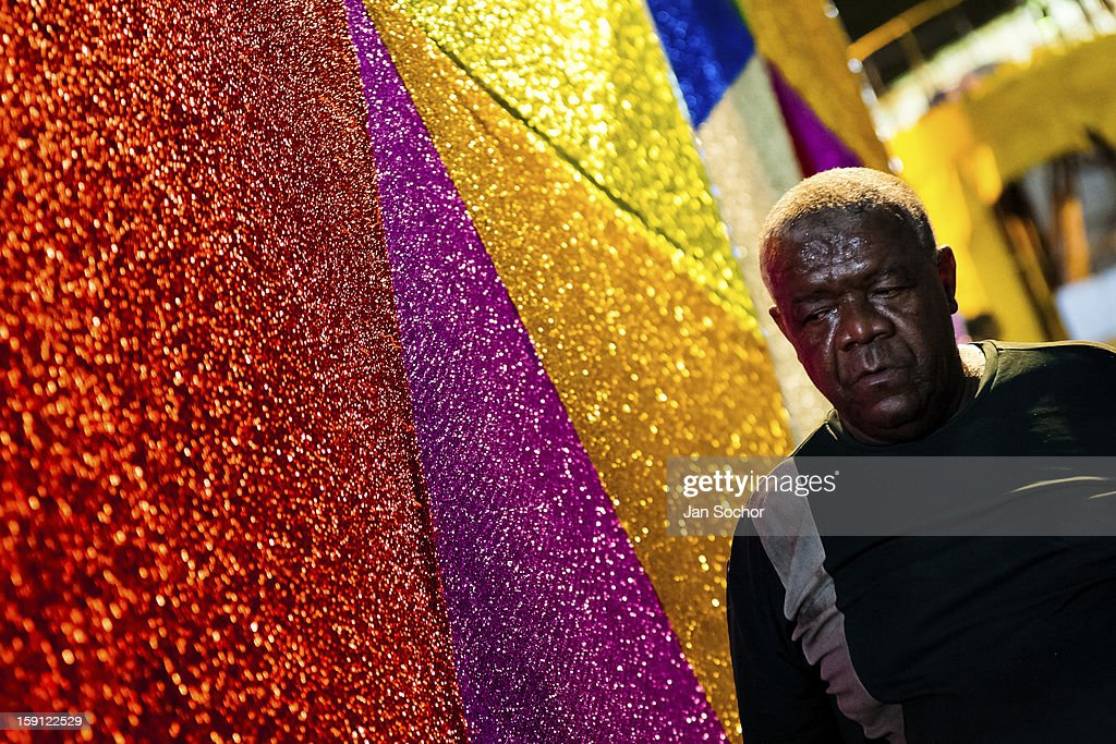 A member of Império Serrano samba school walks along on a carnival float inside the workshop in Rio de Janeiro, Brazil, 13 February 2012. The carnival preparations start early in July or August, some 7-8 months before the main samba schools parade at the sambodrome. Samba schools hire teams of professional designers and artists who, according to the original theme selected by the school directors and then featured by the school during the parade, create allegorical floats, costumes, sculptures, music, choreography and the entire school show. However, the most of the everyday work in the carnival hangars is performed by unknown but fully dedicated samba schools members.