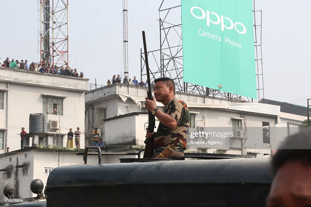 A member of Indian security forces holds a rifle as a wild elephant that strayed into the town walks on the streets of Siliguri in West Bengal state, India, on February 10, 2016. A full-grown wild elephant went on a rampage through a West Bengal town on Wednesday, damaging up to 100 houses before eventually being subdued with tranquilliser guns.