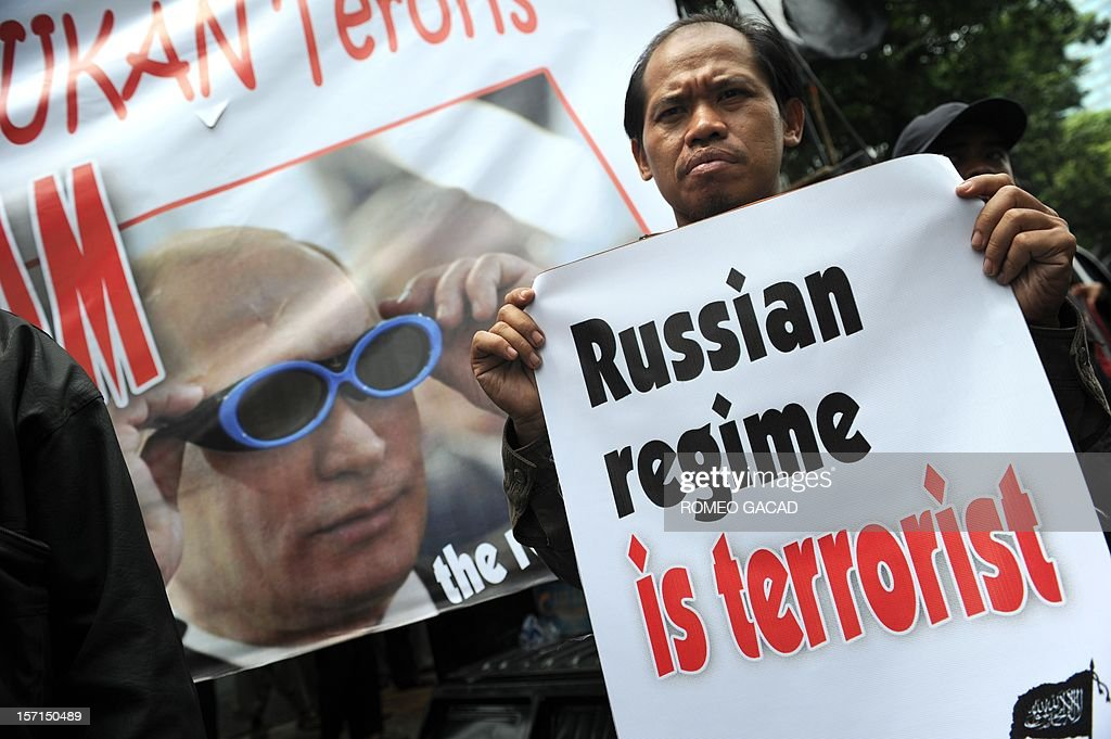 A member of Indonesia's Islamist group Hizb ut-Tahrir holds a placard in front of a portrait of Russian Prime Minister Vladimir Putin (L) during a protest outside the Russian embassy in Jakarta on November 29, 2012. Around 200 Indonesians from the Islamist group Hizb ut-Tahrir rallied outside the embassy, demanding the release of six of its leaders and accusing Moscow of planting weapons to smear them.