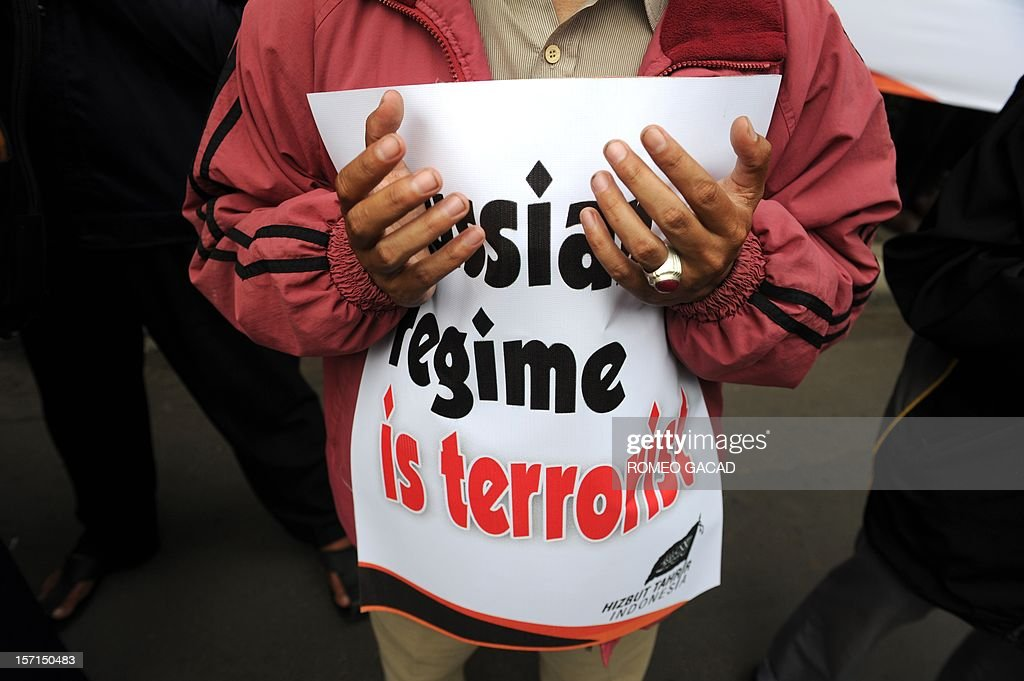 A member of Indonesia's Islamist group Hizb ut-Tahrir prays with a placard stating 'Russian regime is terrorist' during a protest outside the Russian embassy in Jakarta on November 29, 2012. Around 200 Indonesians from the Islamist group Hizb ut-Tahrir rallied outside the embassy, demanding the release of six of its leaders and accusing Moscow of planting weapons to smear them.