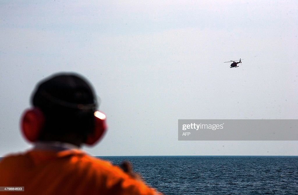 A member of Indonesia's National Search and Rescue looks on as a helicopter flies over the waters during search operations in the Andaman sea area around northern tip of Indonesia's Sumatra island for the missing Malaysian Airlines flight MH370 on March 21, 2014. The search for MH370 has been compared to that of an Air France jet that crashed into the Atlantic Ocean in 2009 with the loss of 228 lives.