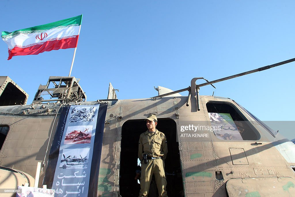 A member of Iran's elite Revolutionary Guard stands under a national flag on the wreckage of a captured US air force CH53 Sea Stallion helicopter...