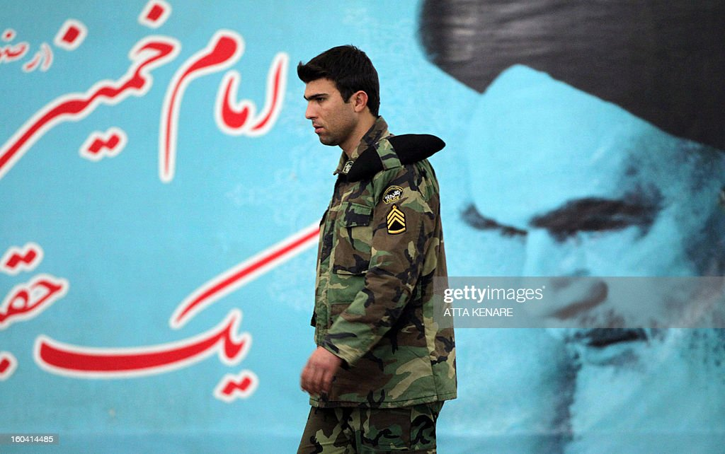 A member of Iran's Revolutionary Guards elite unit walks past a giant poster featuring the founder of Iran's Islamic Republic, Ayatollah Ruhollah Khomeini during a ceremony marking the 34th anniversary of his return from exile on January 31, 2013 at Khomeini's mausoleum in Tehran. Bells chimed across Iran to mark his return from exile in 1979, the trigger for a revolution which spawned an Islamic state now engulfed in a deep political crisis.