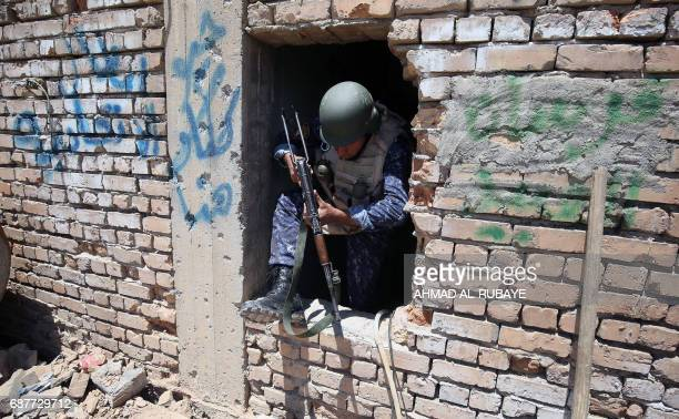 TOPSHOT A member of Iraqi forces climbs out of a house on the frontline in the old city of Mosul on May 24 during the ongoing offensive to retake the...
