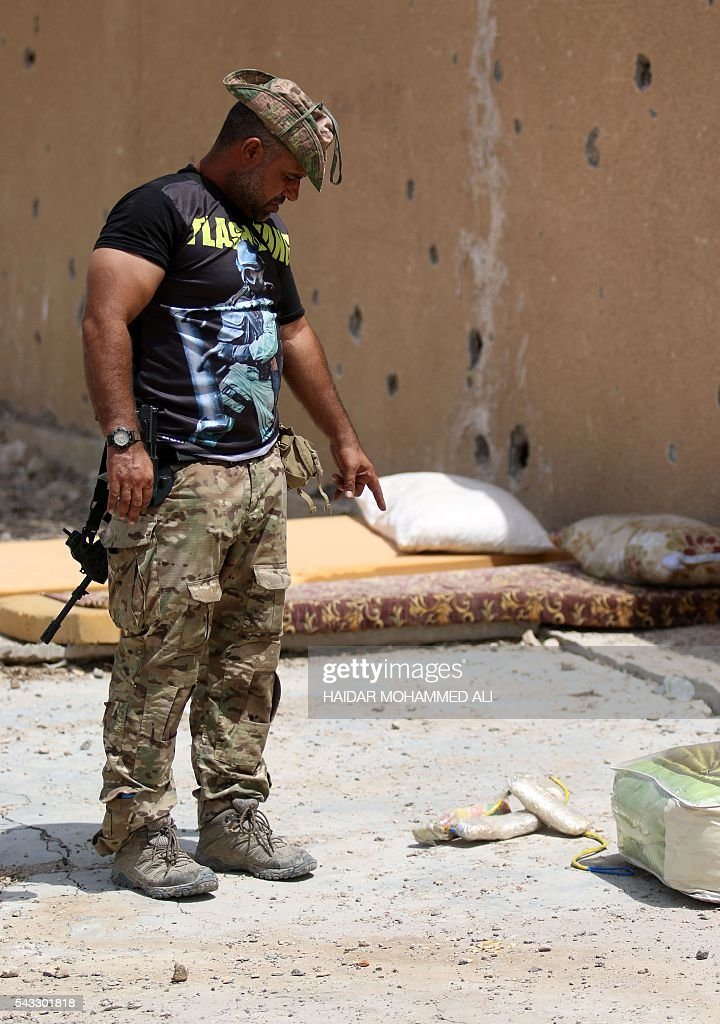 A member of Iraqi government forces points at explosives on the ground on June 27, 2016 in western Fallujah, 50 kilometres (30 miles) from the Iraqi capital Baghdad, after Iraqi forces retook the embattled city from the Islamic State group. Iraqi forces took the Islamic State group's last positions in the city of Fallujah on June 26, 2016, establishing full control over one of the jihadists' most emblematic bastions after a month-long operation. ALI