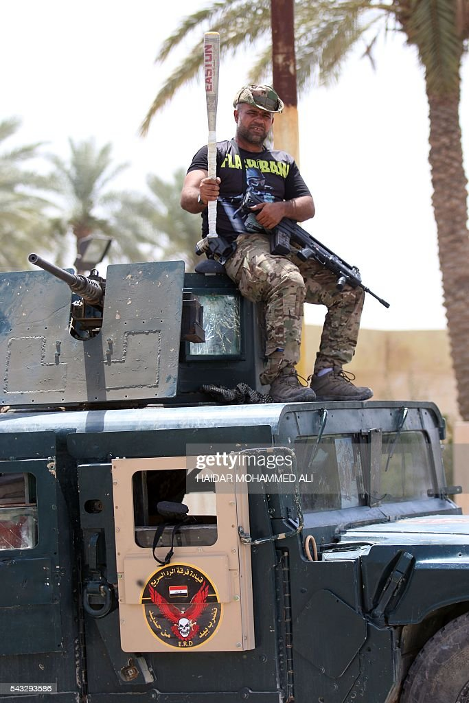 A member of Iraqi government forces poses on his armoured vehicle with a bat on June 27, 2016 in western Fallujah, 50 kilometres (30 miles) from the Iraqi capital Baghdad, after Iraqi forces retook the embattled city from the Islamic State group. Iraqi forces took the Islamic State group's last positions in the city of Fallujah on June 26, 2016, establishing full control over one of the jihadists' most emblematic bastions after a month-long operation. ALI
