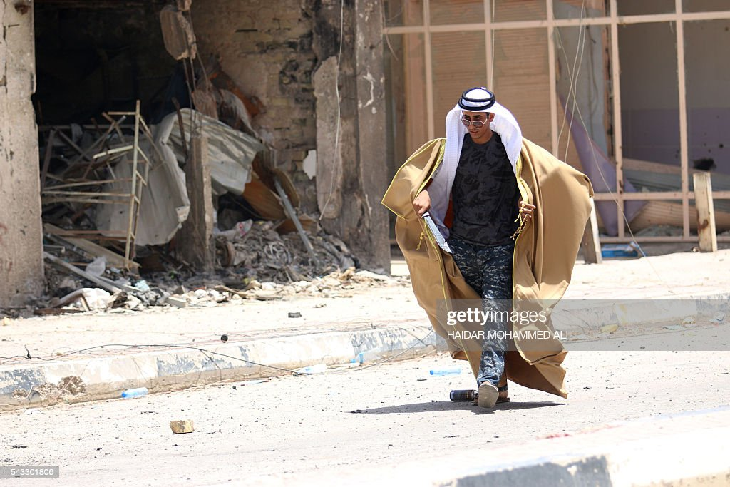 A member of Iraqi police forces is dressed with a traditional Arab attire as he celebrates on a street on June 27, 2016 in western Fallujah, 50 kilometres (30 miles) from the Iraqi capital Baghdad, after Iraqi forces retook the embattled city from the Islamic State group. Iraqi forces took the Islamic State group's last positions in the city of Fallujah on June 26, 2016, establishing full control over one of the jihadists' most emblematic bastions after a month-long operation. ALI