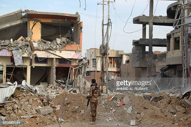 TOPSHOT A member of Iraqi progovernment forces stands amid the rubble of destroyed buildings in the Hoz neighbourhood in central Ramadi the capital...
