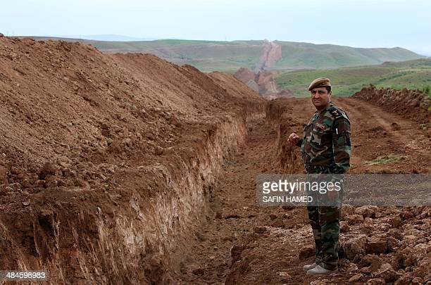 A member of Iraqi security forces looks on during the digging operations to build a trench on the northern Iraqi border with Syria to prevent people...
