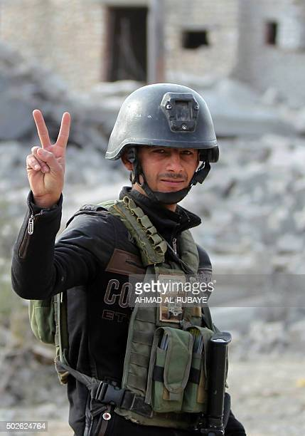A member of Iraq's elite counterterrorism service flashes the 'V' for victory sign on December 27 2015 in the Hoz neighbourhood in central Ramadi the...