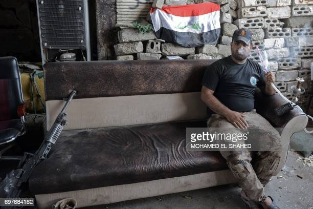A member of Iraq's elite CounterTerrorism Service smokes a waterpipe while on a break during the advance towards the Old City of Mosul on June 19...