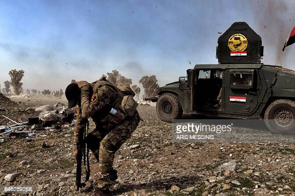 TOPSHOT A member of Iraq's elite Rapid Response Division tries to shielf himself during an explosion during the assault to retake the northern city...