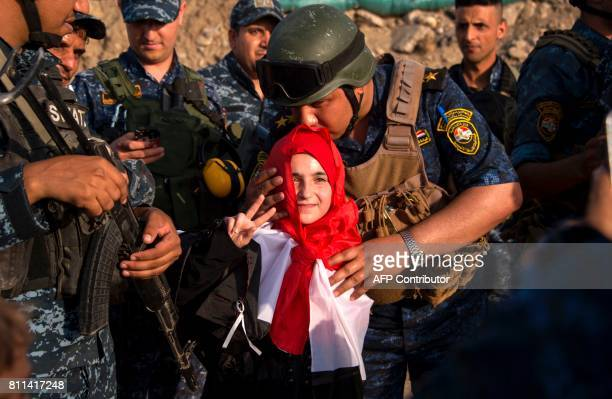 TOPSHOT A member of Iraq's federal police kisses a girl as forces celebrate in the Old City of Mosul on July 9 2017 after the government's...