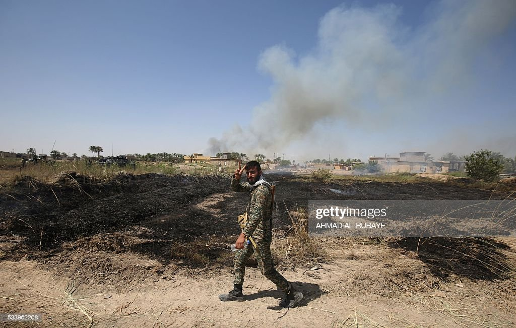A member of Iraq's pro-government forces flashes the 'V' for victory sign as smoke billows in the background near the city of Fallujah on May 24, 2016 during an assault to retake the city from jihadists of Islamic State (IS) group. Iraqi forces, consisting of special forces, soldiers, police, militia forces and pro-government tribesmen, launched a major assault to retake Fallujah, the scene of deadly battles during the US occupation and one of the toughest targets yet in Baghdad's war on the Islamic State group. RUBAYE