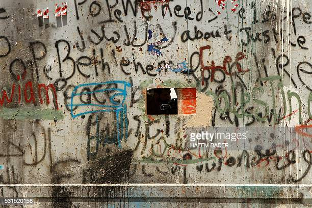 TOPSHOT A member of Israeli security forces aims through a hole in the iron gate along the Israeli controversial separtion barrier on May 15 2016 in...