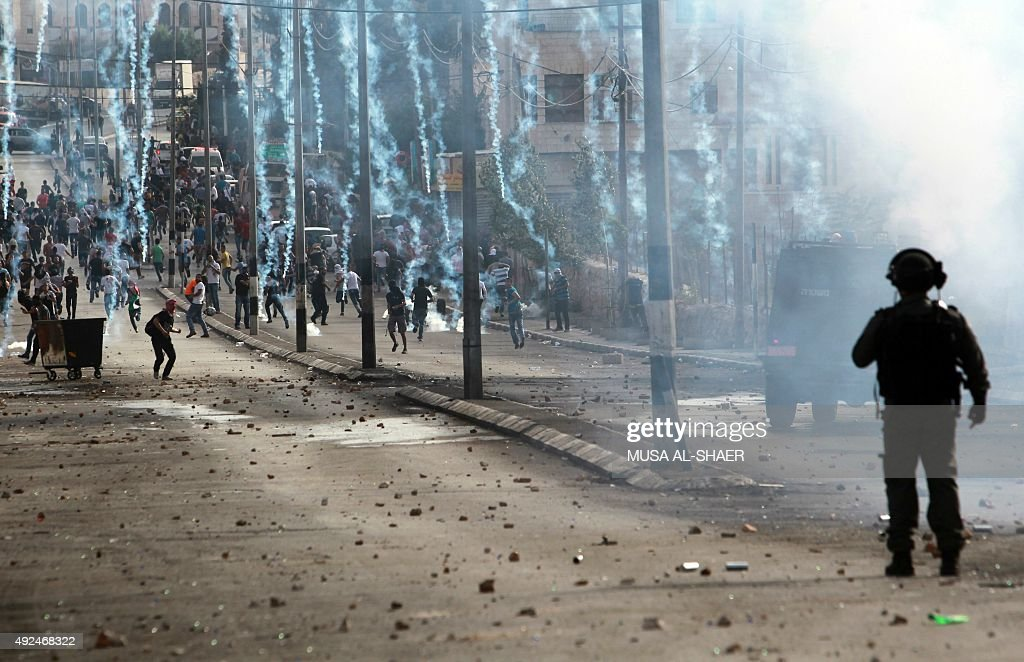 A member of Israeli security forces stands guard in front of Palestinian stone throwers running away from tear gas during clashes on October 13 2015...