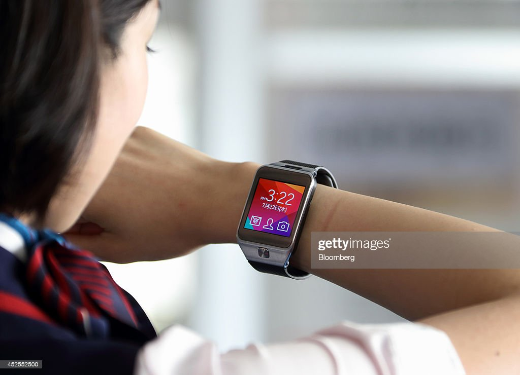 A member of Japan Airlines Co ground staff talks on a Samsung Galaxy Gear 2 Lite smartwatch manufactured by Samsung Electronics Co as she works on...