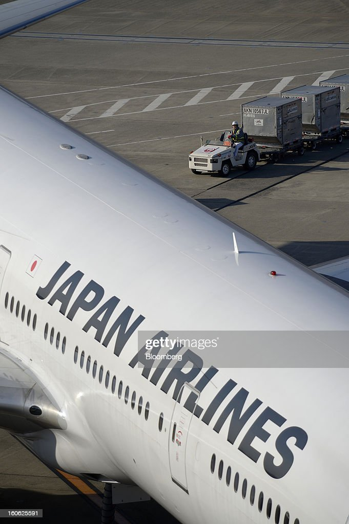 A member of Japan Airlines Co.'s (JAL) ground staff drives a cart transporting luggage containers as a JAL aircraft is parked on the tarmac at Haneda Airport in Tokyo, Japan, on Sunday, Feb. 3, 2013. Japan Airlines, the nation's largest carrier by market value, is scheduled to release earnings on Feb. 4. Photographer: Akio Kon/Bloomberg via Getty Images