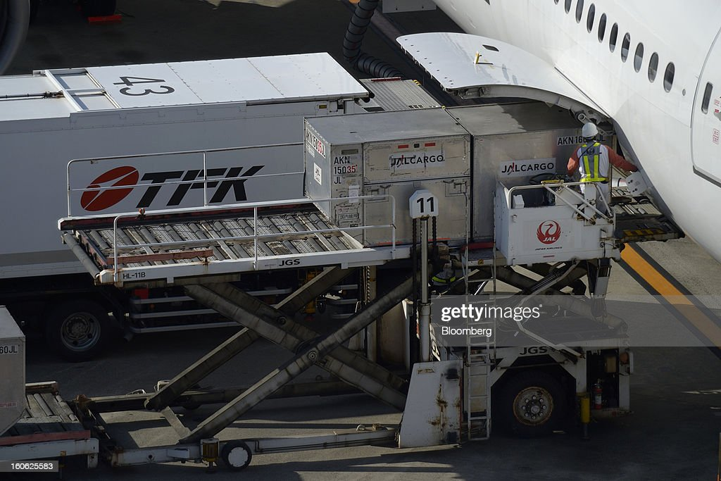 A member of Japan Airlines Co.'s ground staff loads cargo containers onto an aircraft at Haneda Airport in Tokyo, Japan, on Sunday, Feb. 3, 2013. Japan Airlines, the nation's largest carrier by market value, is scheduled to release earnings on Feb. 4. Photographer: Akio Kon/Bloomberg via Getty Images