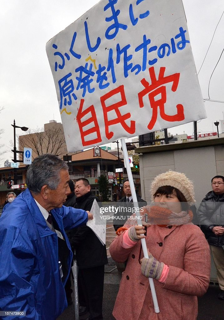 A member (L) of Japan's main opposition Liberal Democratic Party (LDP) tells an anti-nuclear protestor (R) holding a placard saying 'LDP built nuclear plants in Fukushima' to leave a meeing of LDP candidate Yoshitami Kameyama (unseen in picture) at Fukushima, northern Japan on December 4, 2012. Campaigning officially started ahead of Japan's December 16 general election. AFP PHOTO / Yoshikazu TSUNO
