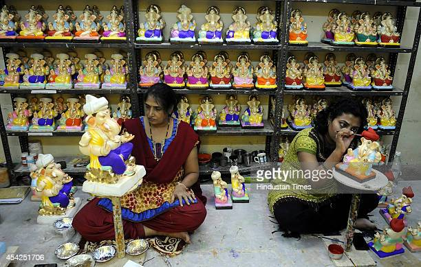 Member of Kavishwar family giving finishing touches to ecofriendly clay idol of Ganesh ahead of Hindu festival of Ganesh Chaturthi on August 26 2014...