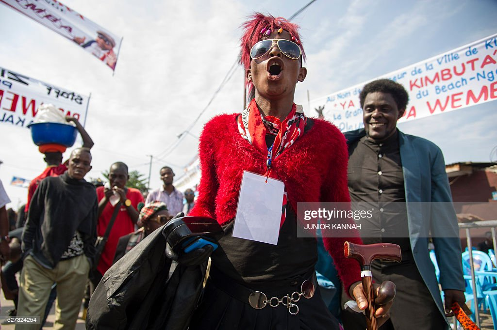 A member of La SAPE movement ('Societe des Ambianceurs et des Personnes Elegantes' or 'Society of Ambiance-Makers and Elegant People') gathers with others in the streets of 'Village Molokoi', in the Matonge neighborhood of Kinshasa, to pay tribute to late rumba musician Papa Wemba on May 2, 2016. Democratic Republic of Congo's rumba king Papa Wemba was posthumously awarded one of his country's highest honours, a week after he collapsed on stage and died aged 66. / AFP / JUNIOR