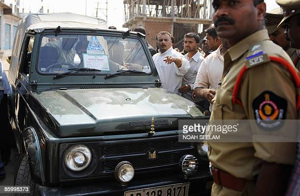 Member of Legislative Assembly Akbaruddin Owaisi hides from the camera as a party worker issues instructions not to photograph during a clash with...