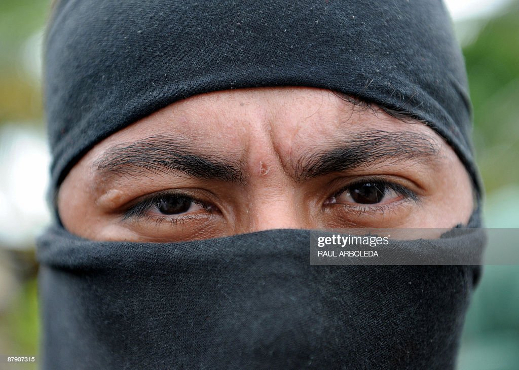 A member of 'Los Rastrojos' bandit group covers his face with a balaclava as he surrenders at the Voltigeros Battalion on May 21 2009 in Uraba...