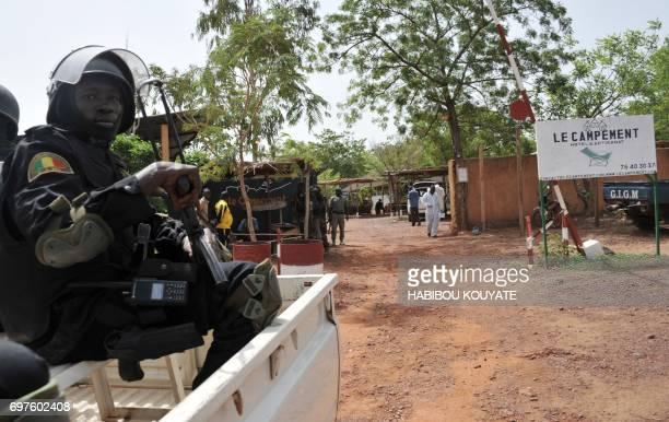 A member of Malian antiterrorist special forces 'Forsat' looks on as investigators walk at the entrance of the Kangaba tourist resort in Bamako on...