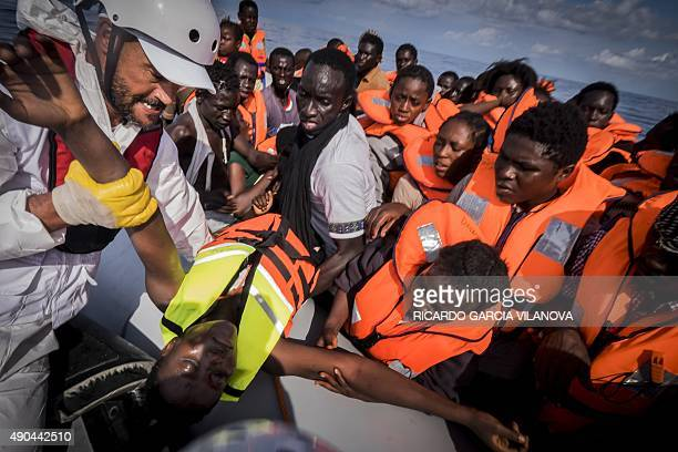 A member of Medecins Sans Frontieres carries a young migrant aboard a zodiac during a rescue operation by the NGO with the Dignity 1 search and...