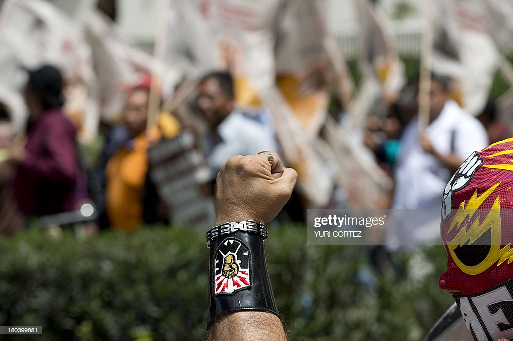 A member of Mexican Electrical Workers (SME) union rises his fist during a rally at Reforma avenue in Mexico City on September 12, 2013. Different civil organizations and unions take the streets to protest against the new educational, energetic and finance reforms announced recently by Mexican President Enrique Pena Nieto. AFP PHOTO/ Yuri CORTEZ
