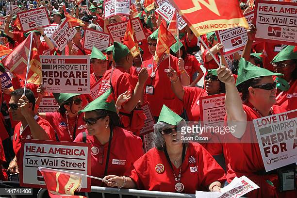 Member of National Nurses United gather with other protestors rally in Daley Plaza calling for a 'Robin Hood' tax on stocks bonds derivatives and...
