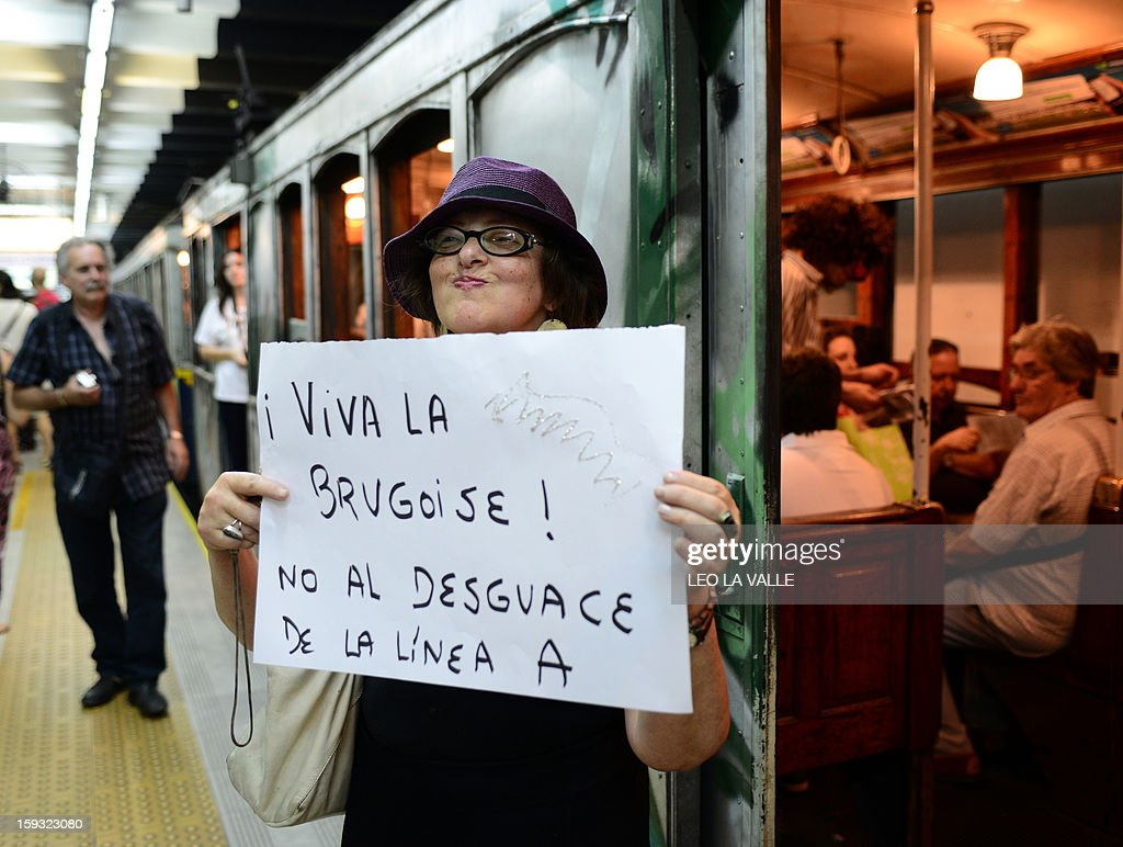 A member of 'Network for heritage' ONG holds a sign to protest against the scrapping of Le Burgeoise wagons of the A Line subway, at Plaza de Mayo station in Buenos Aires, on January 11, 2013 during the so called last ride of the historic trains. The Line A will be closed betwen January 12 and March 8 following a decision by Buenos Aires city Mayor Mauricio Macri to replace the fleet with Chinese-made wagons. Line A was the first subway line to work in the southern hemisphere and its trains are among the ten oldest still working daily. The La Brugeoise wagons were constructed between 1912 and 1919 by La Brugeoise et Nicaise et Delcuve in Belgium. AFP PHOTO/Leo La Valle
