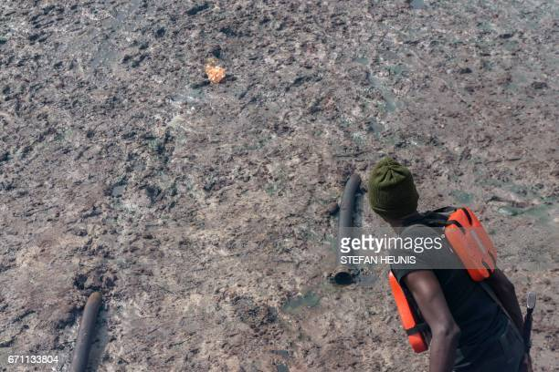 A member of NNS Pathfinder of the Nigerian Navy forces points out an illegal oil refinery pipe outlet on April 19 2017 in the Niger Delta region near...