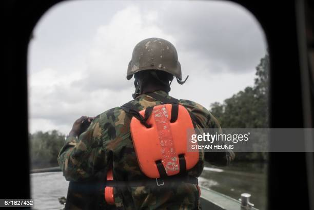 A member of NNS Pathfinder of the Nigerian Navy forces stands on the back of a gunboat patrolling in the creeks to look for illegal oil refineries on...