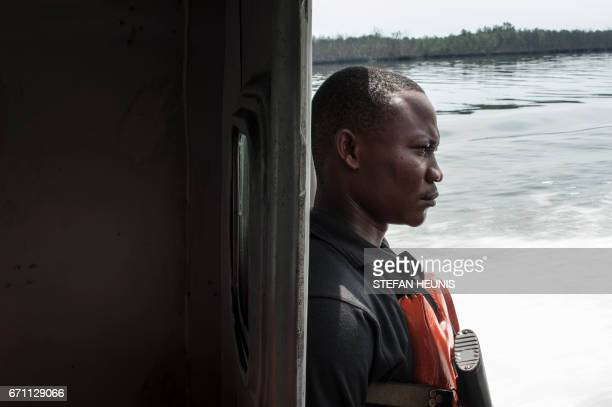 A member of NNS Pathfinder of the Nigerian Navy forces surveys his surroundings from the back of a gunboat on a patrol in the creeks looking for...